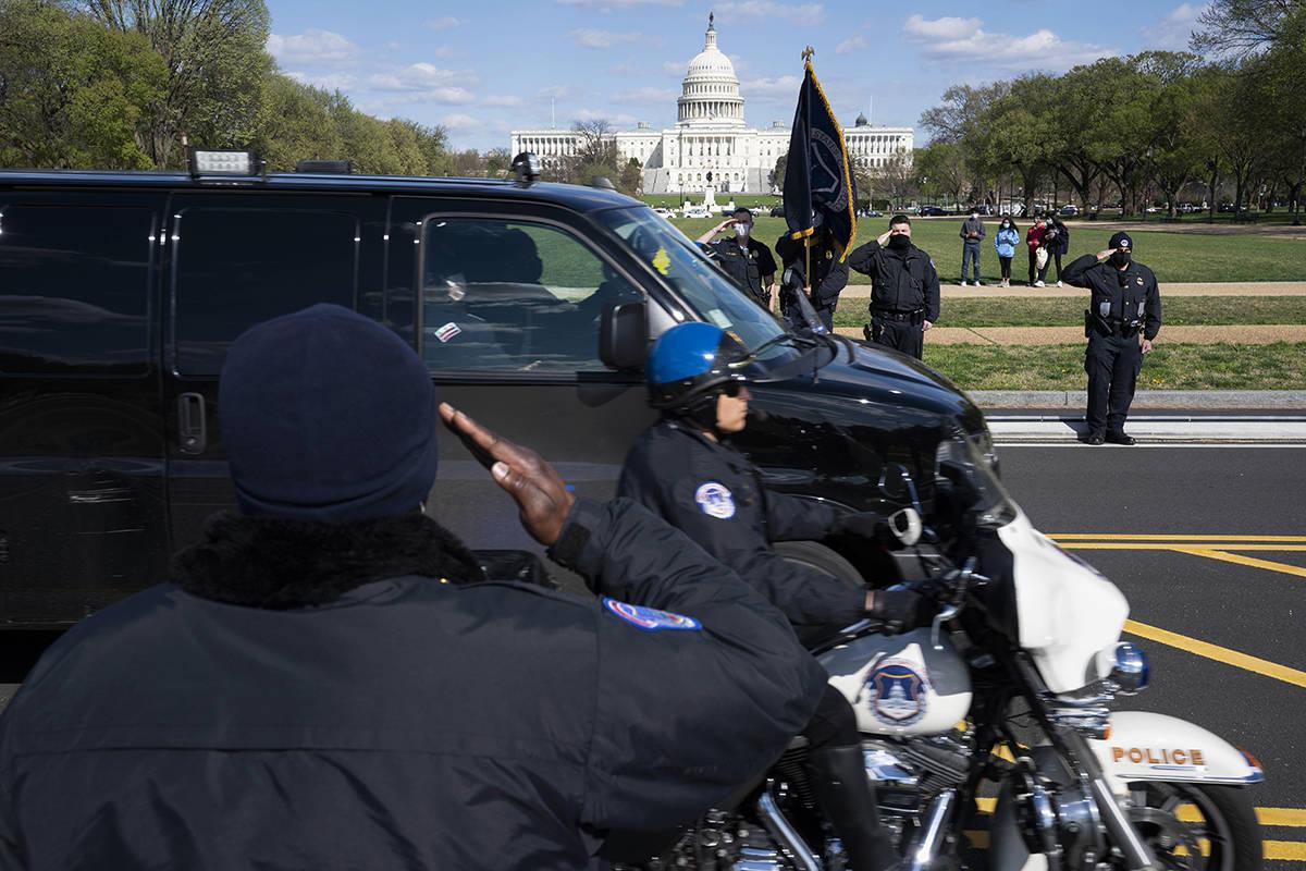 Con el Capitolio de EE.UU. al fondo, los oficiales de la Policía del Capitolio de EE.UU. salud ...