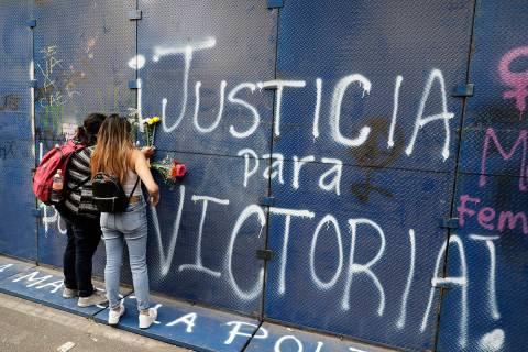 Mujeres colocan flores en el muro perimetral de las oficinas del estado de Quintana Roo rociada ...