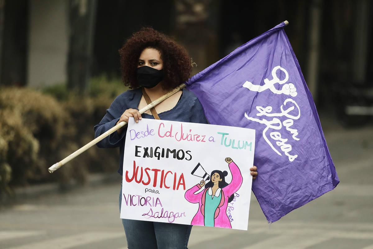 """Una mujer sostiene una bandera feminista y un cartel que dice """"De Ciudad Juárez a Tulum exigim ..."""