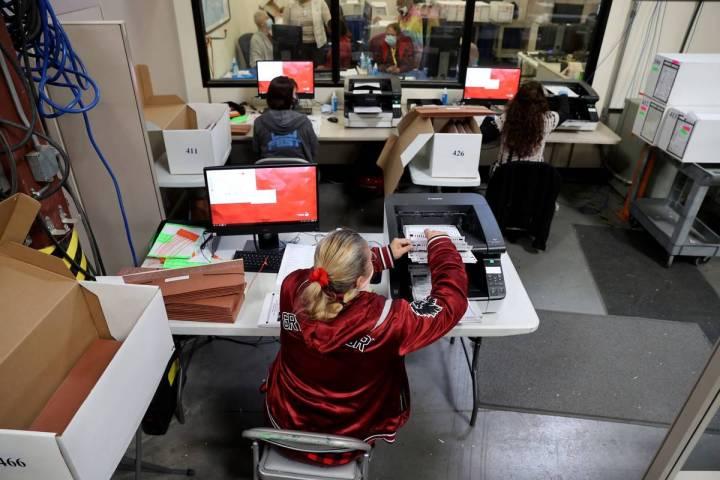 El personal del Departamento Electoral del Condado trabaja en el recuento en la carrera del Dis ...