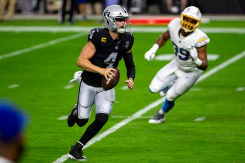 El quarterback de los Raiders, Derek Carr (4), lucha con el balón mientras el cornerback de lo ...