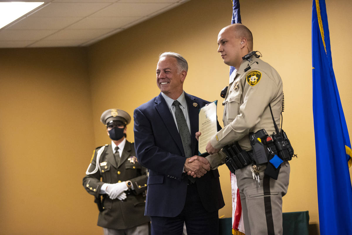El alguacil Joe Lombardo entrega al agente de policía Jovan Magazin un premio por sus esfuerzo ...