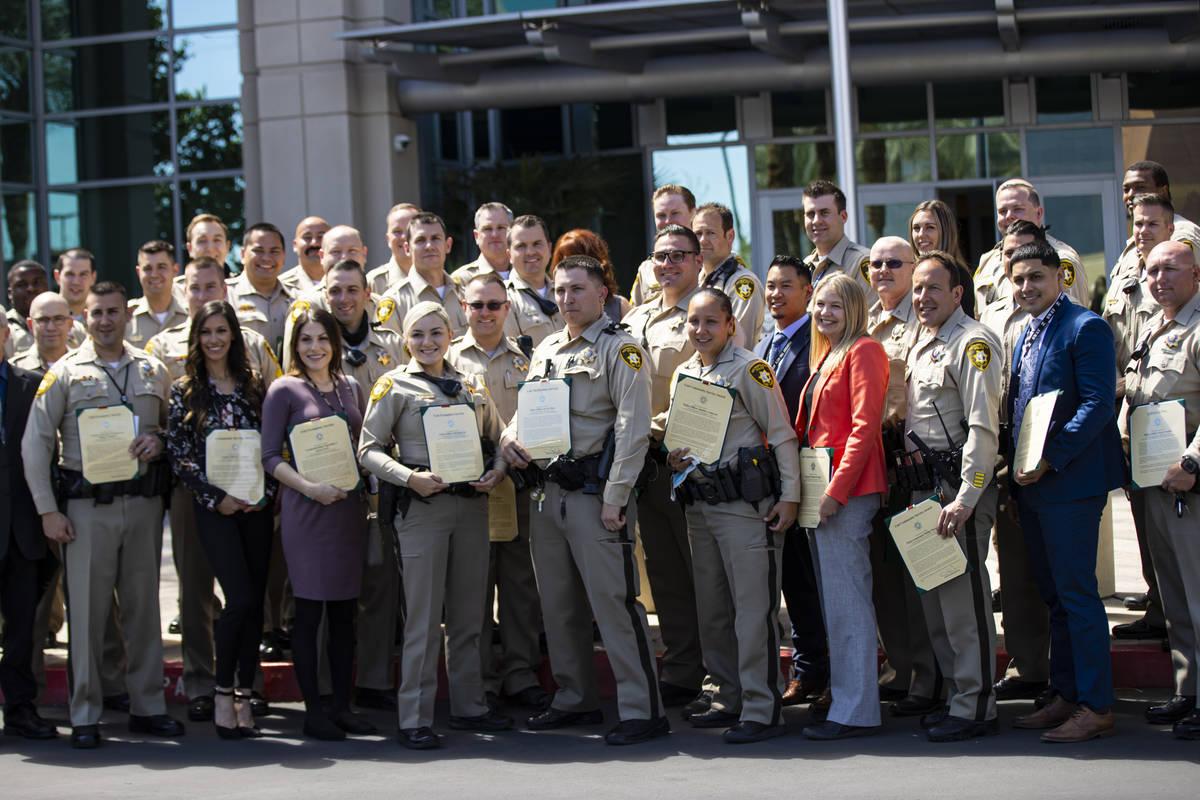 Agentes y empleados del Departamento de Policía Metropolitana posan para una foto grupal con s ...