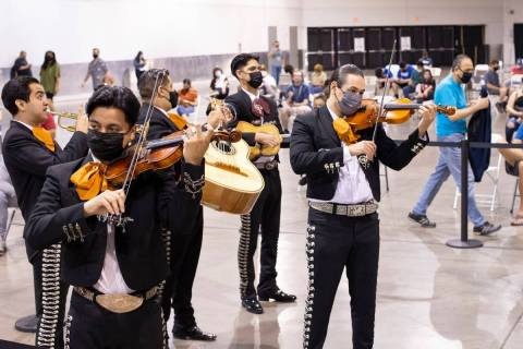 Mariachi Nuestras Raíces se presenta en una sala de personas que esperan en la fila para recib ...