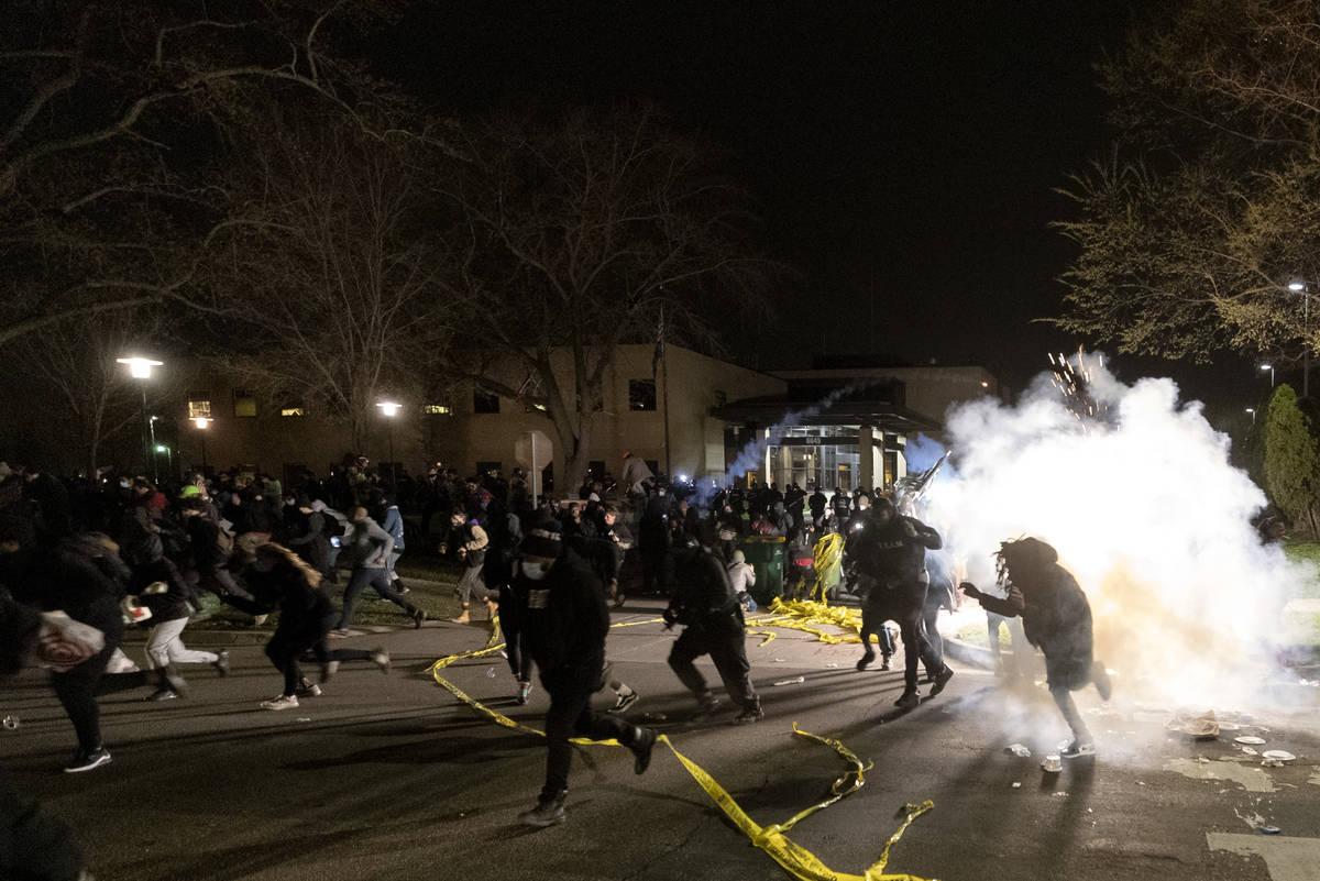 Gente corre mientras la policía intenta dispersar a la multitud en el Departamento de Policía ...