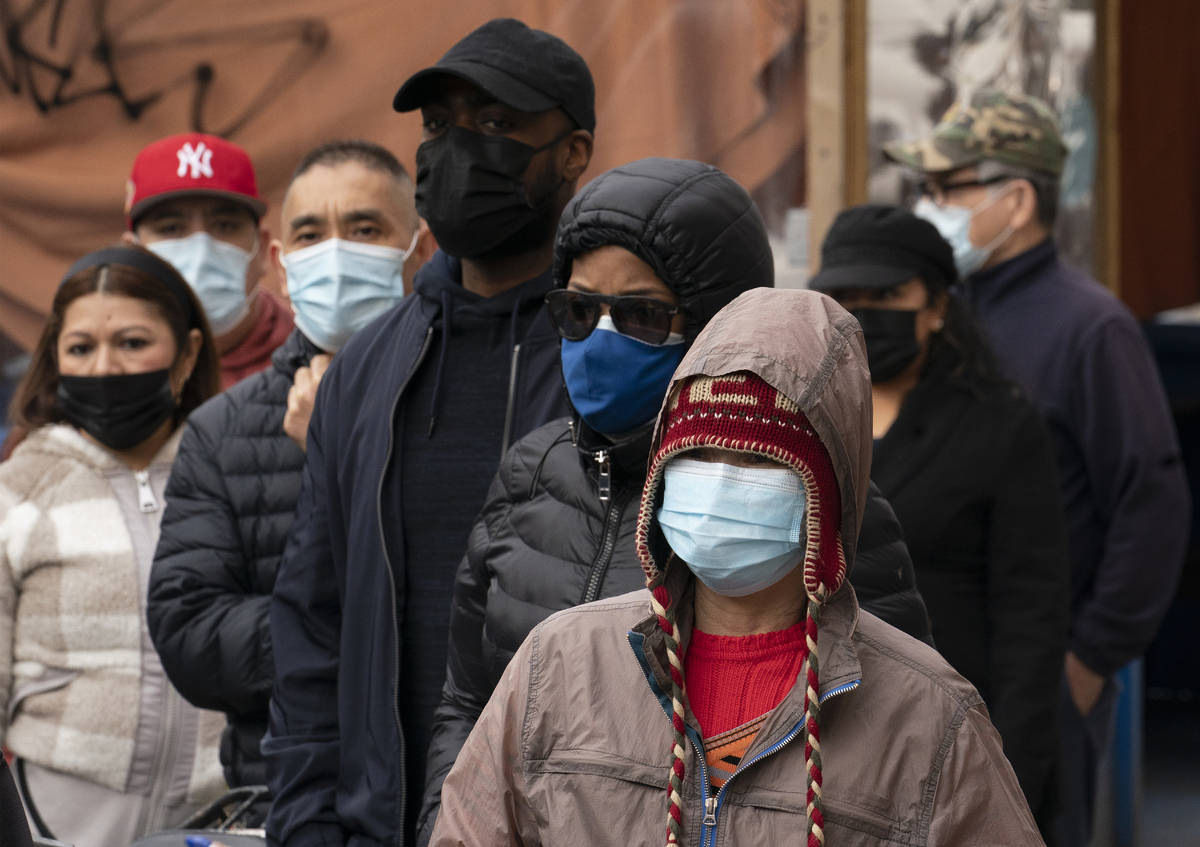 Trabajadores de restaurantes y repartidores esperan en fila para apuntarse a la vacuna COVID-19 ...