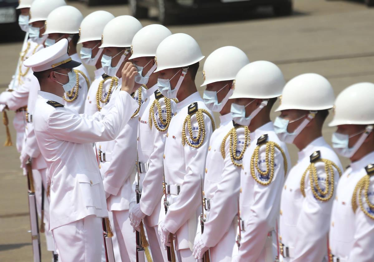 Un capitán de la guardia de honor de la Marina de Taiwán ajusta la máscara facial de un miem ...