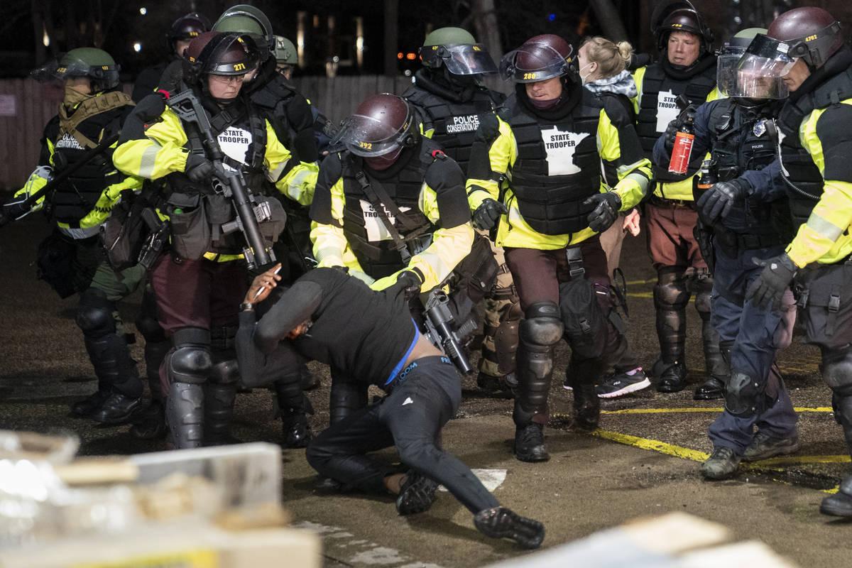 Un manifestante es arrestado por la policía por violar el toque de queda y una orden de disper ...