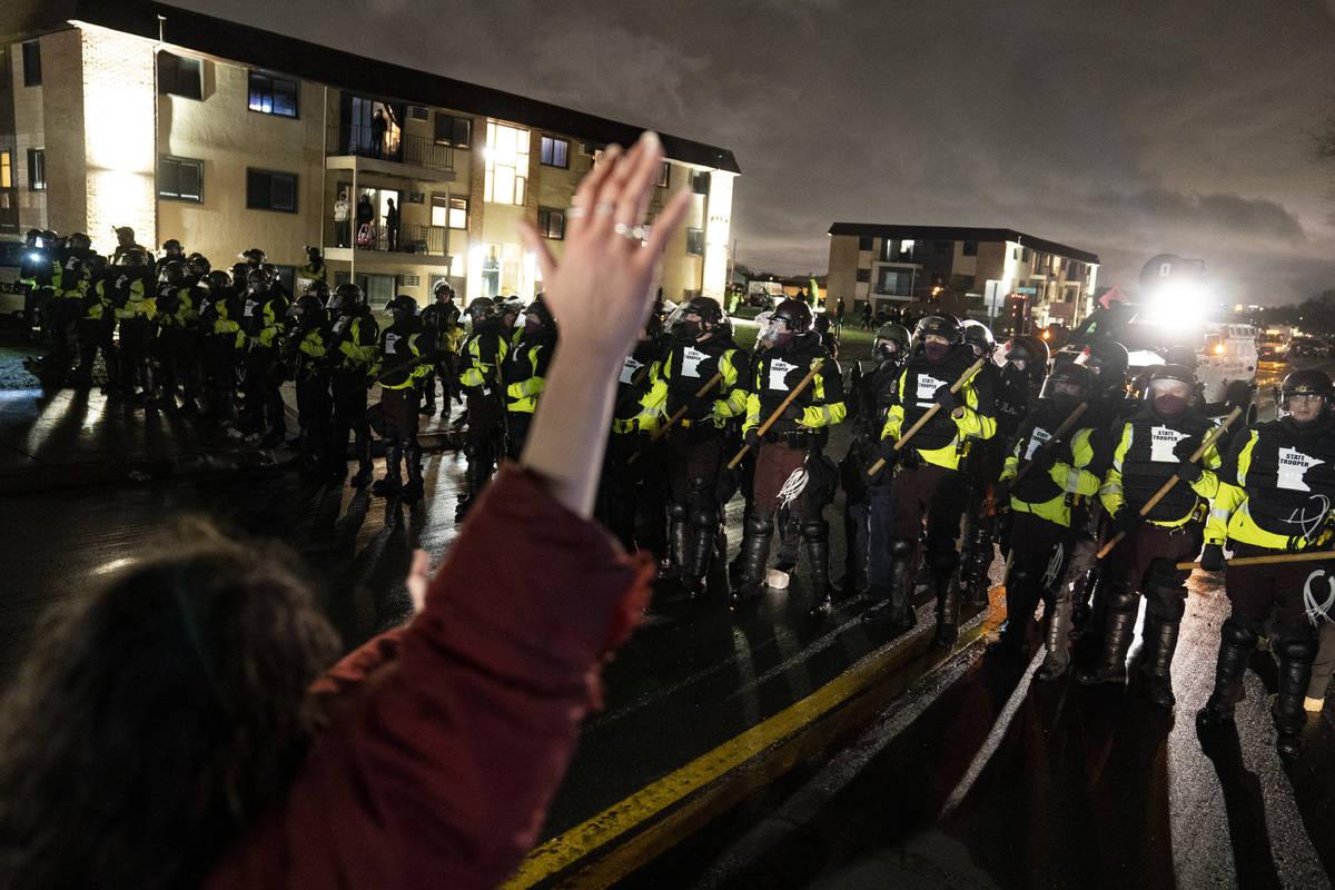 Un manifestante levanta la mano mientras se enfrenta a un perímetro de policías mientras desa ...