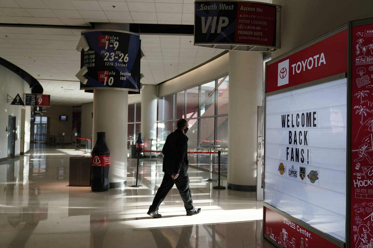 Un hombre pasa junto a un cartel que da la bienvenida a los fans antes de un partido de hockey ...