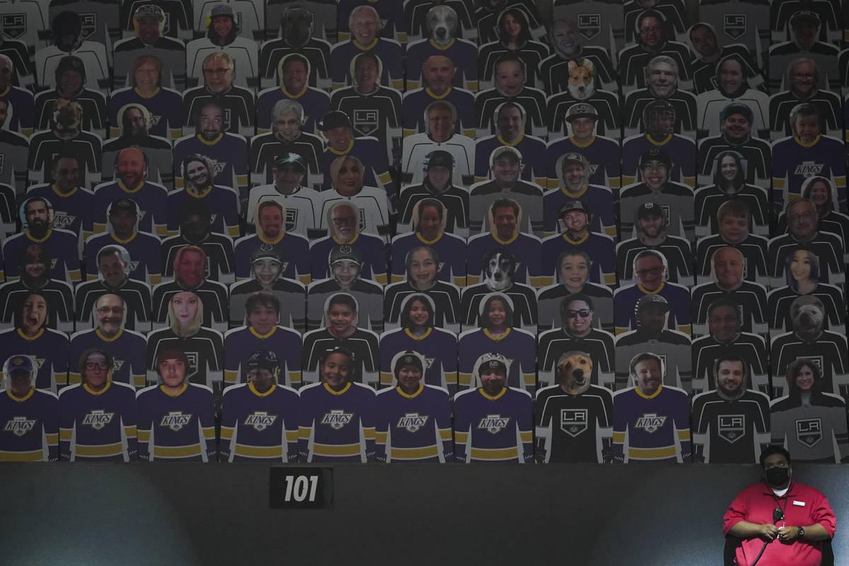 Un acomodador se sitúa junto a una sección de recortes de fans en las gradas en un partido de ...