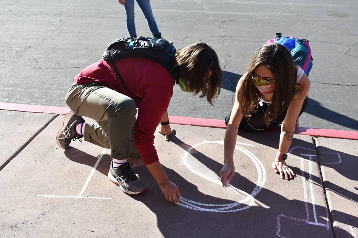 """Dos manifestantes, David y Caitlyn, escriben con tiza la frase """"Justice for Jorge Gómez"""" e ..."""