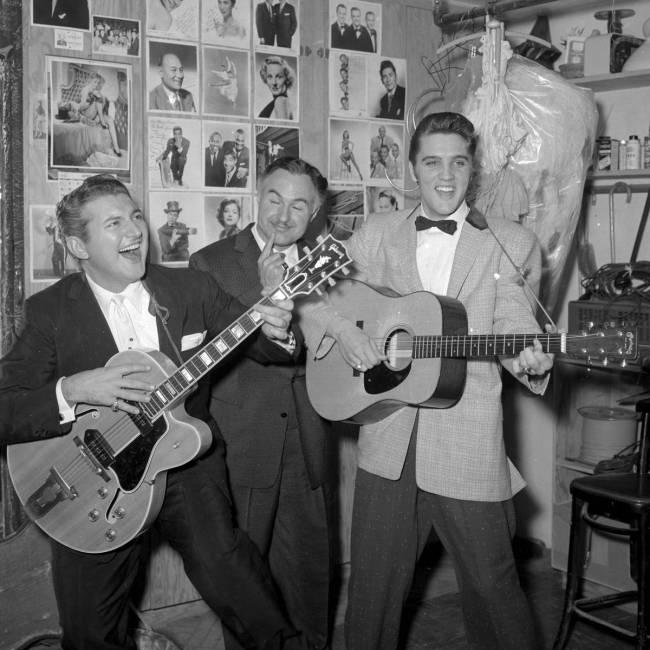 Liberace bromea con una guitarra mientras él y su hermano George Liberace visitan a Elvis Pres ...