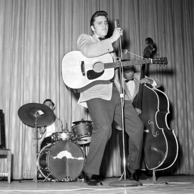 Elvis Presley canta, junto con D.J. Fontana a la batería y Bill Black al bajo, en Venus Room d ...