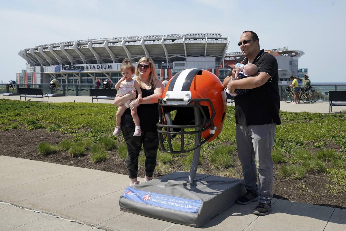 Fans posan para una foto con un gran casco de los Cleveland Browns el martes, 27 de abril de 20 ...