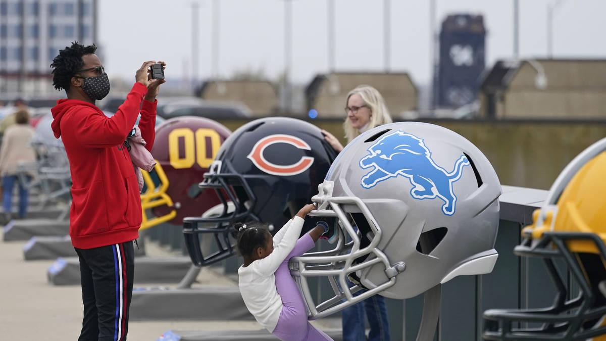 Un hombre toma una foto donde se exhiben los cascos de los 32 equipos el sábado, 24 de abril d ...