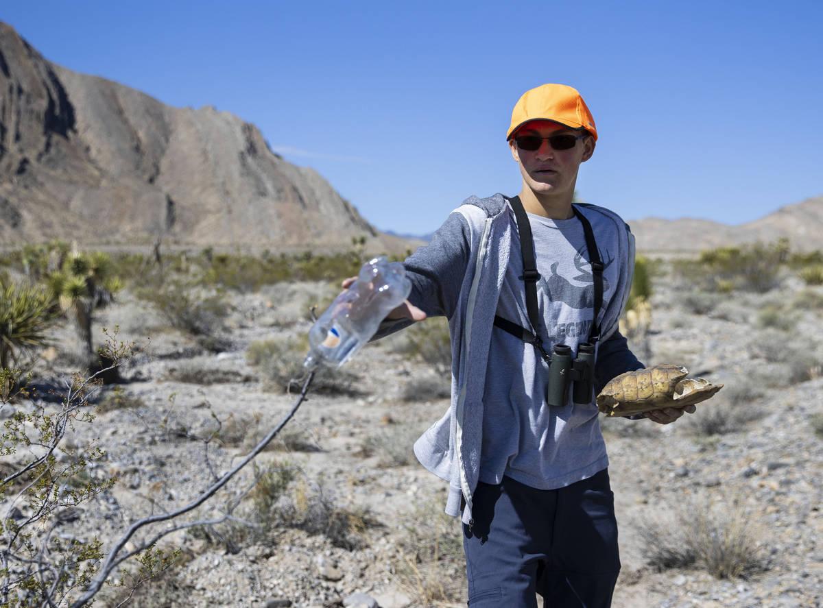 Christian Daniels, de 15 años, sosteniendo un caparazón de tortuga, recupera una botella de p ...