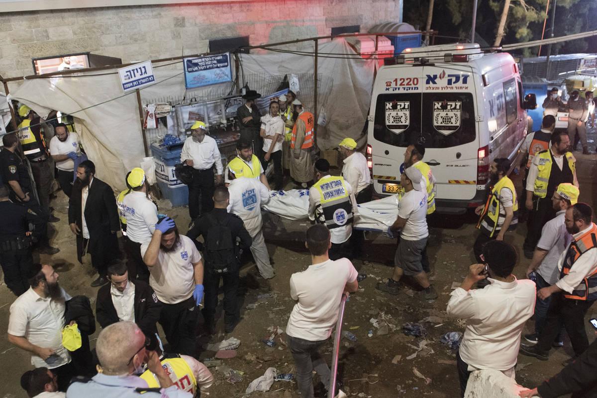 Funcionarios de seguridad israelíes y rescatistas llevan el cuerpo de una víctima que murió ...