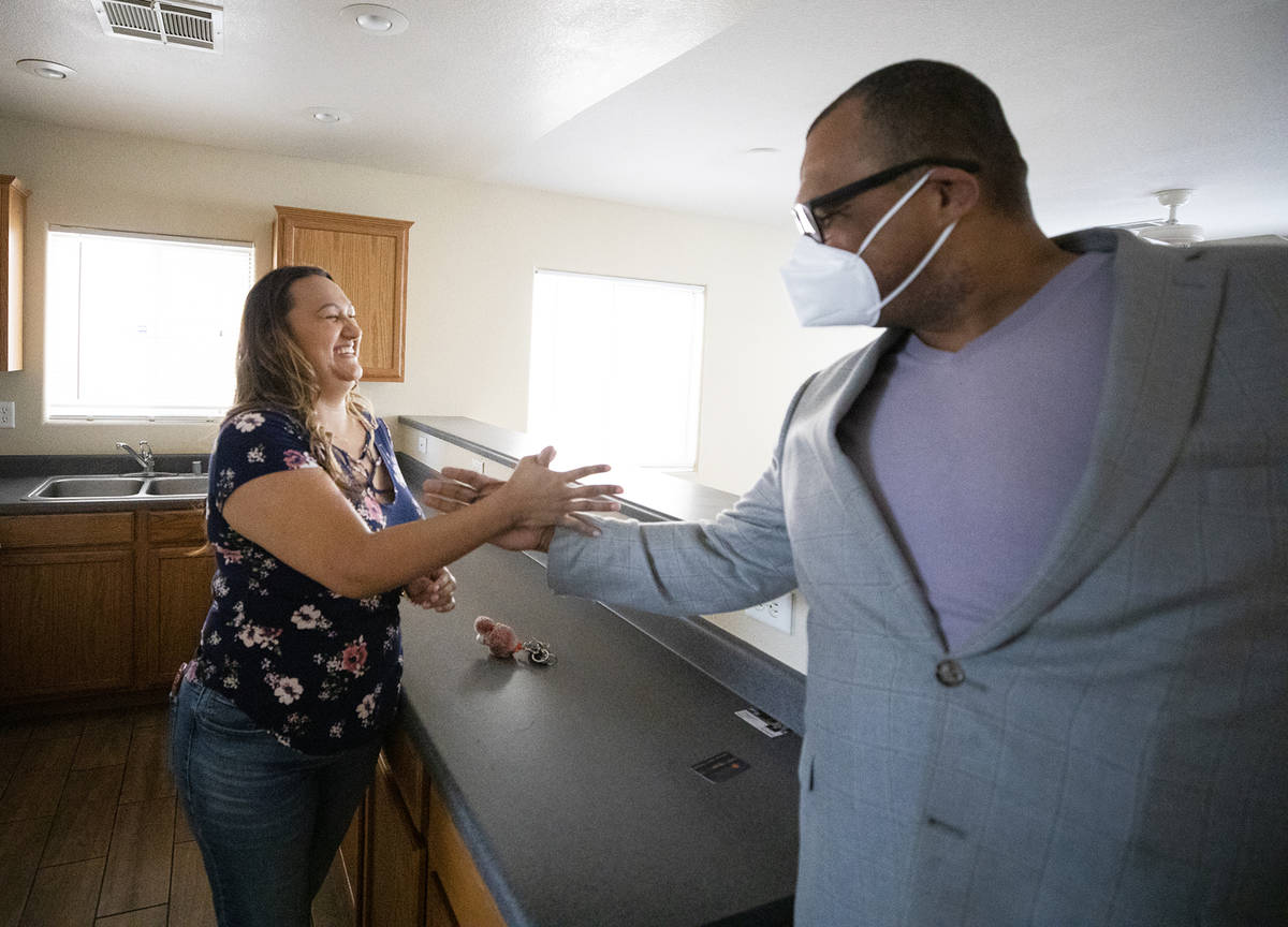 Amy Phinsee, a la izquierda, choca el puño y estrecha la mano con el agente inmobiliario Cassi ...