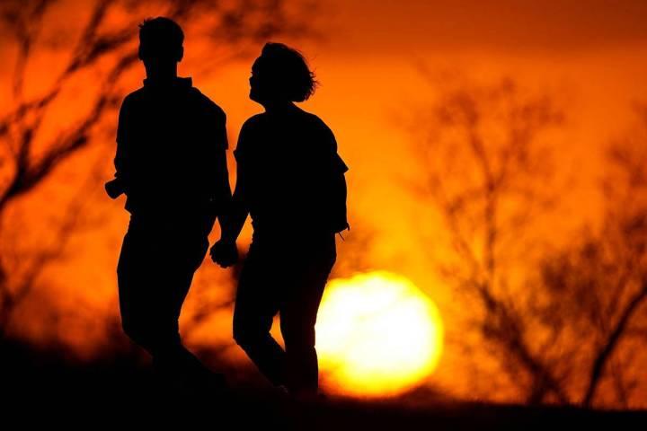 Una pareja camina por un parque al atardecer, el miércoles 10 de marzo de 2021, en Kansas City ...