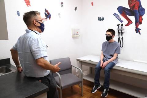 El doctor Michael Levin, pediatra de Henderson, habla con Trent Thurman, de 12 años, participa ...