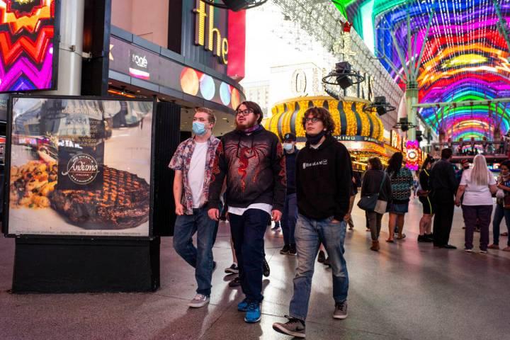 Personas, algunas con máscaras y otras no, caminan por Fremont Street Experience en el centro ...