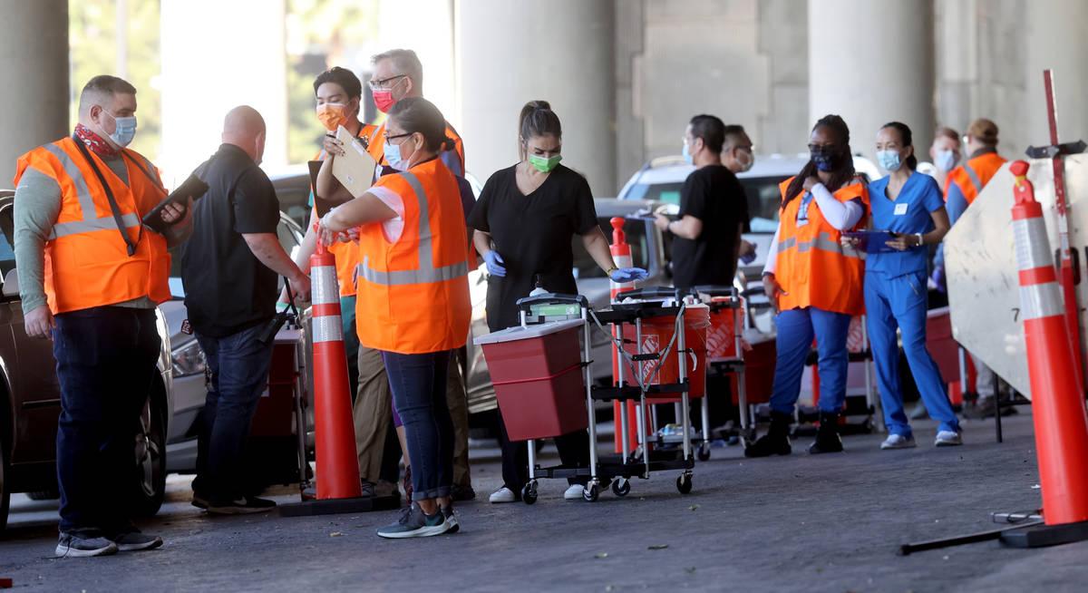 Trabajadores se preparan en una clínica drive-thru de vacunas contra COVID-19 en Bronze Lot de ...