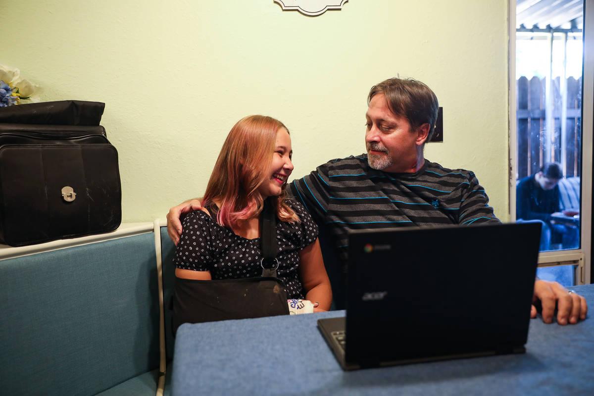 Isabella Wetsel, de 12 años, trabaja en su tarea con su padre Don Collins en su casa de Las Ve ...