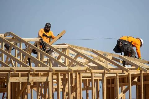 Trabajadores de la construcción construyen nuevas casas cerca de W Elkhorn Road y N Aviary Way ...