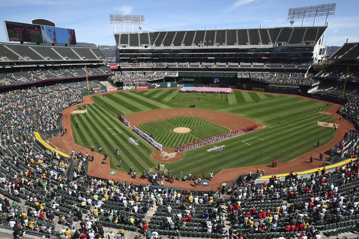 Los Los Angeles Angels y Oakland Athletics se paran para el himno nacional en el Oakland Colise ...