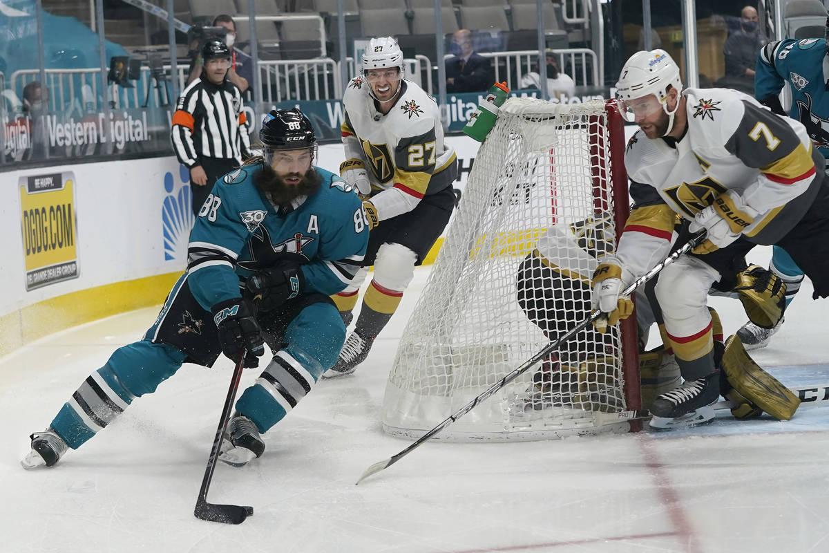El defensa de los San José Sharks, Brent Burns (88), patina contra los defensores de los Vegas ...