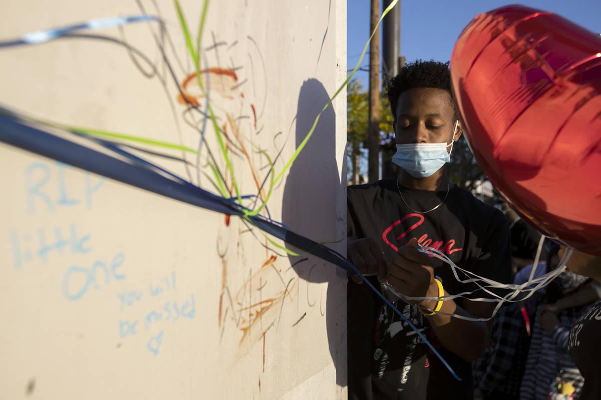 Darreon Hollis ata un globo a un pilar durante una vigilia por Amari Nicholson, de dos años, f ...