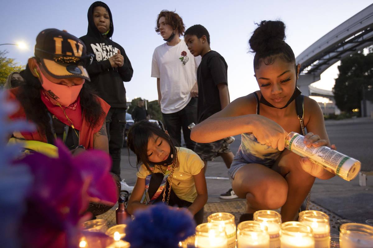 Ariyanah Nobriga, a la derecha, enciende velas durante una vigilia por Amari Nicholson, de dos ...