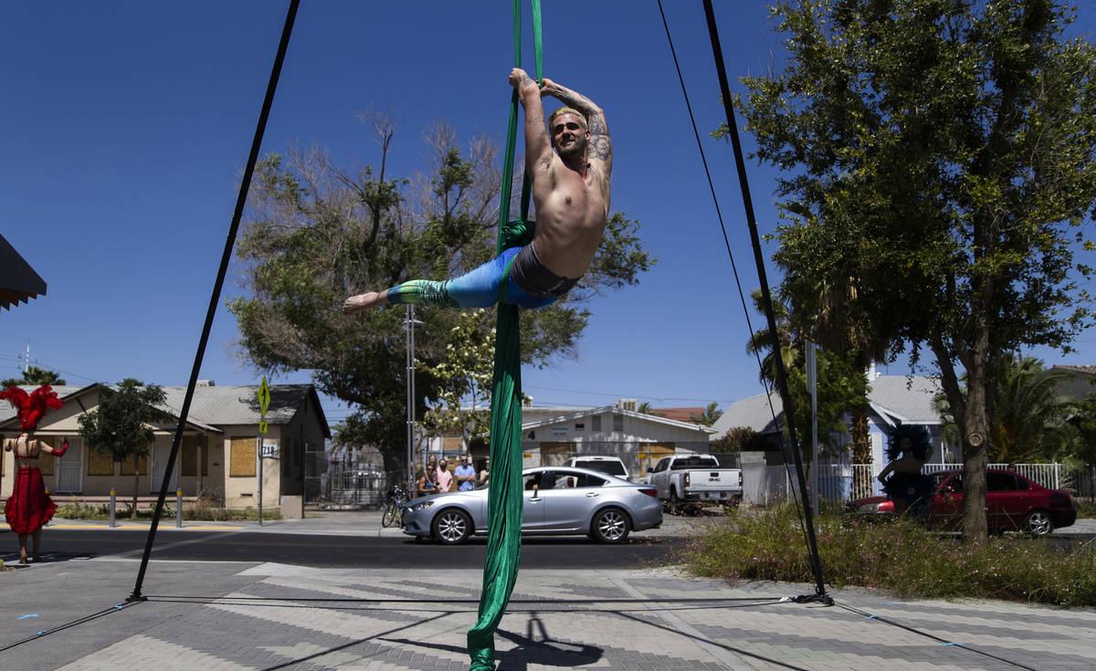 El artista de las sedas aéreas Derek McGinnis actúa para los coches que pasan durante el desf ...