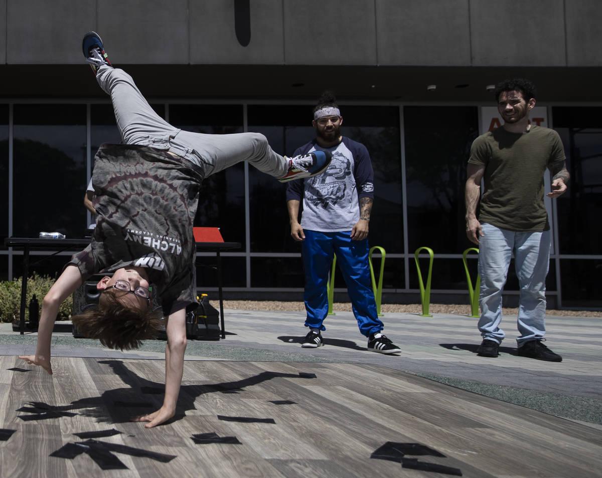 Roves Carreira, a la izquierda, con Alchemy Breaking Academy, bailan en la acera durante el des ...