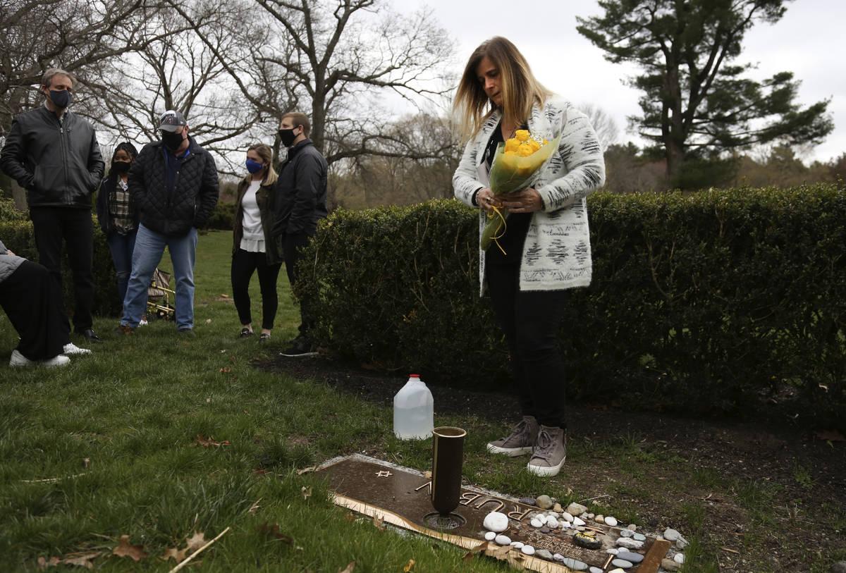 Michelle Pepe coloca un ramo de rosas amarillas en la tumba de su padre mientras sus familiares ...