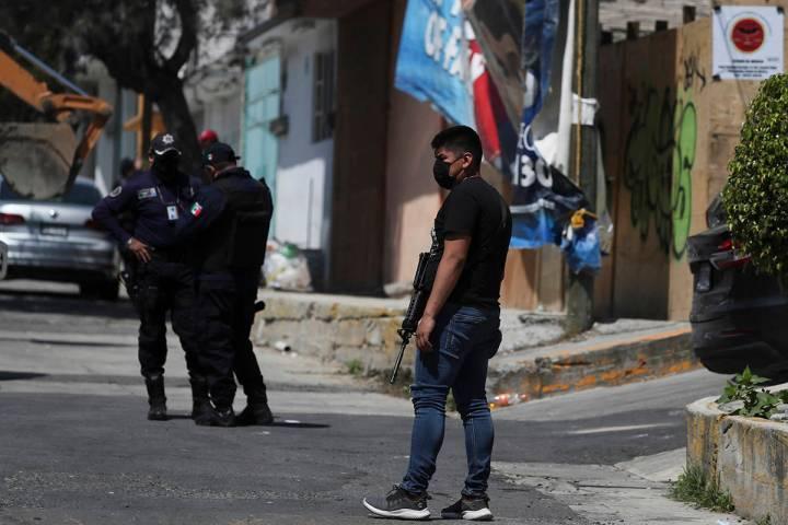 Un oficial de policía hace guardia afuera de la casa donde encontraron huesos debajo del piso ...