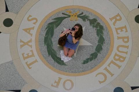 Un visitante se detiene en la rotonda del Capitolio del Estado para tomar fotos el jueves, 20 d ...