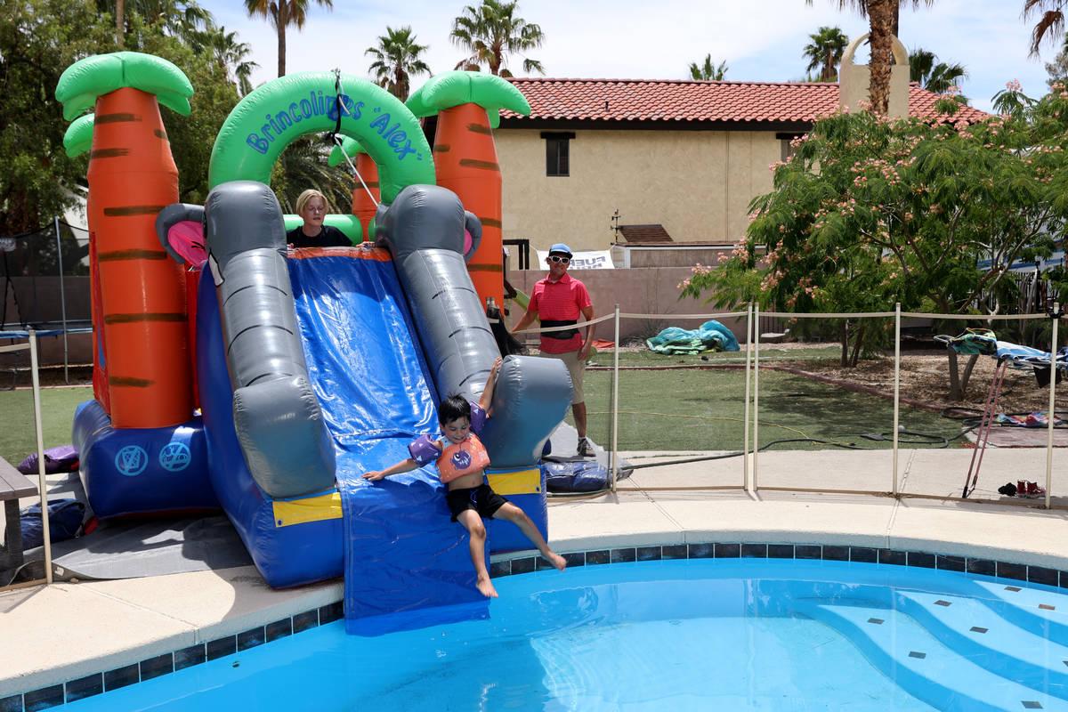 Benjamin David Hairr, de cuatro años, y Genesis Marie Hairr, de seis, se deslizan en la piscin ...