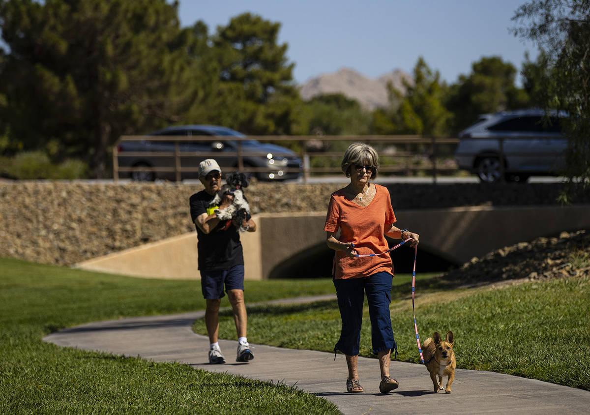 Carol Liberty pasea a su perro, Mikey, mientras Phil Sardo, llevando a su perro, Mei Mei, camin ...