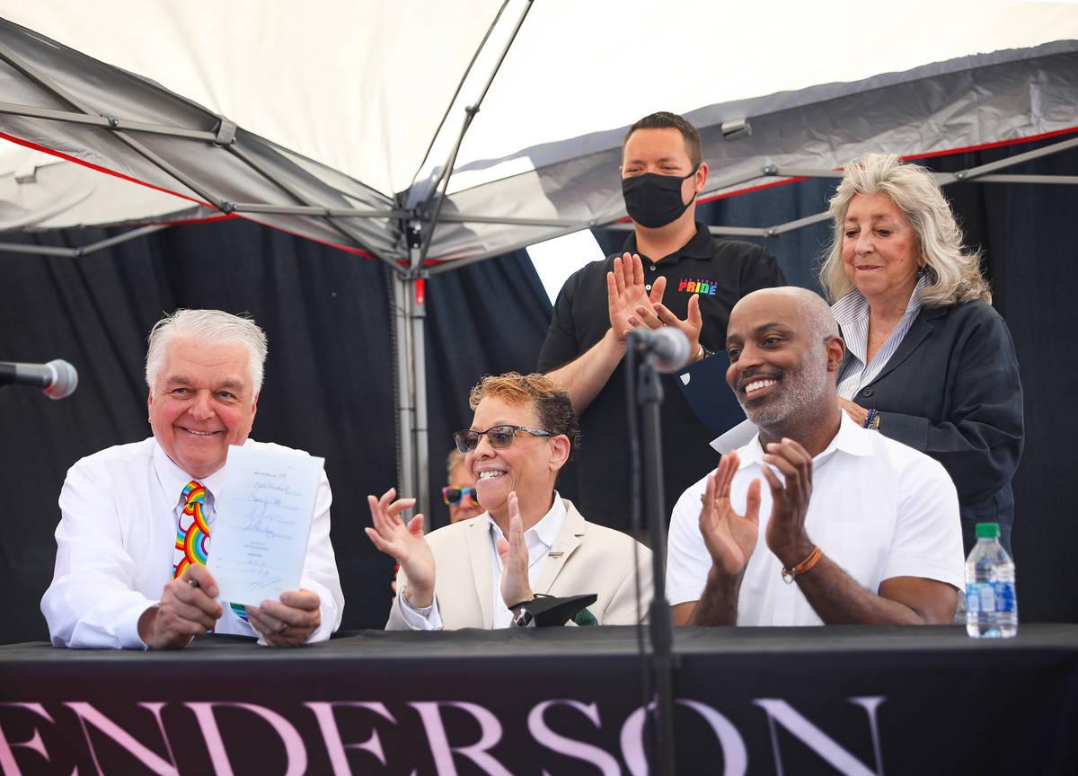El gobernador Steve Sisolak, a la izquierda, sostiene uno de los proyectos de ley que firmó qu ...