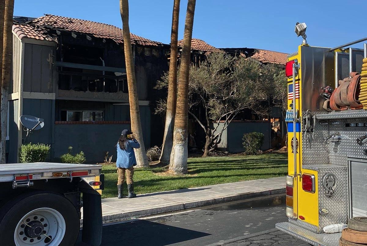 Los daños causados por el fuego en un techo se pueden ver mientras los bomberos del Condado Cl ...