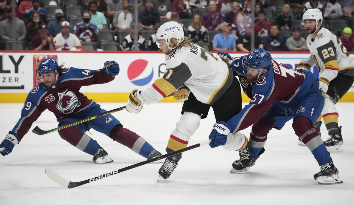 El centro de los Vegas Golden Knights William Karlsson, al centro, conduce entre el defensor de ...