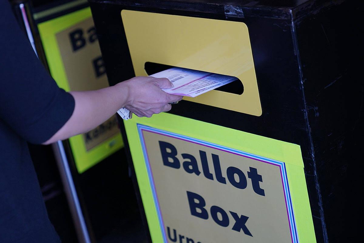 En esta foto de archivo del 29 de octubre de 2020, una persona deposita un voto por correo en u ...