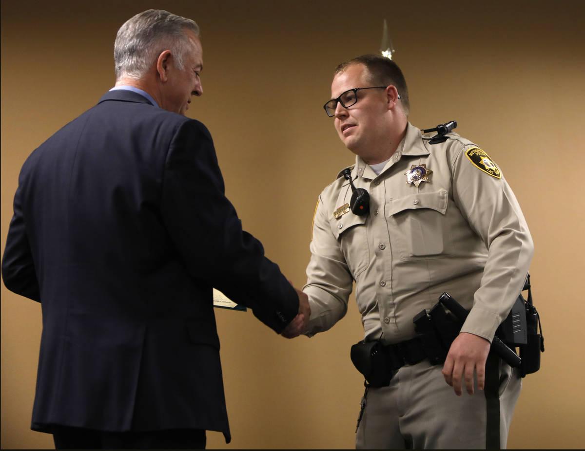 El alguacil del Condado Clark, Joe Lombardo, a la izquierda, estrecha la mano del agente Christ ...