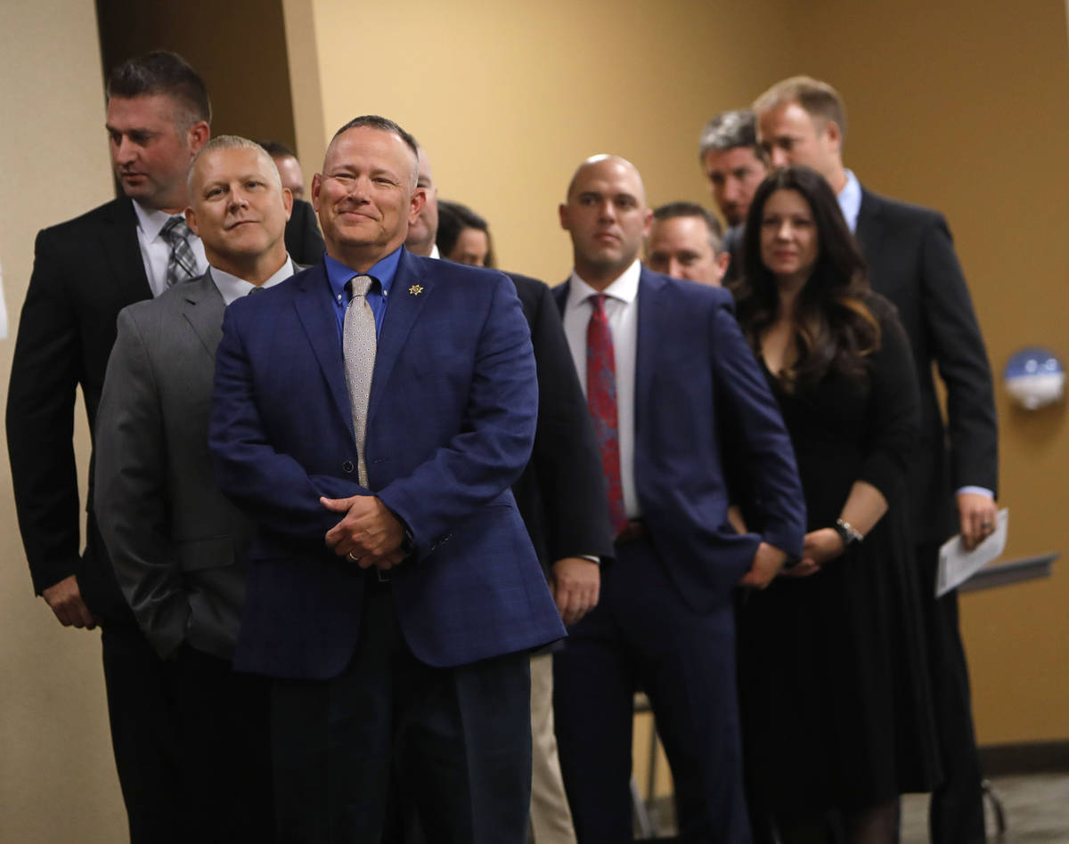 El sargento Randy Dockery, en primer plano al centro, y otros miembros de la unidad esperan par ...