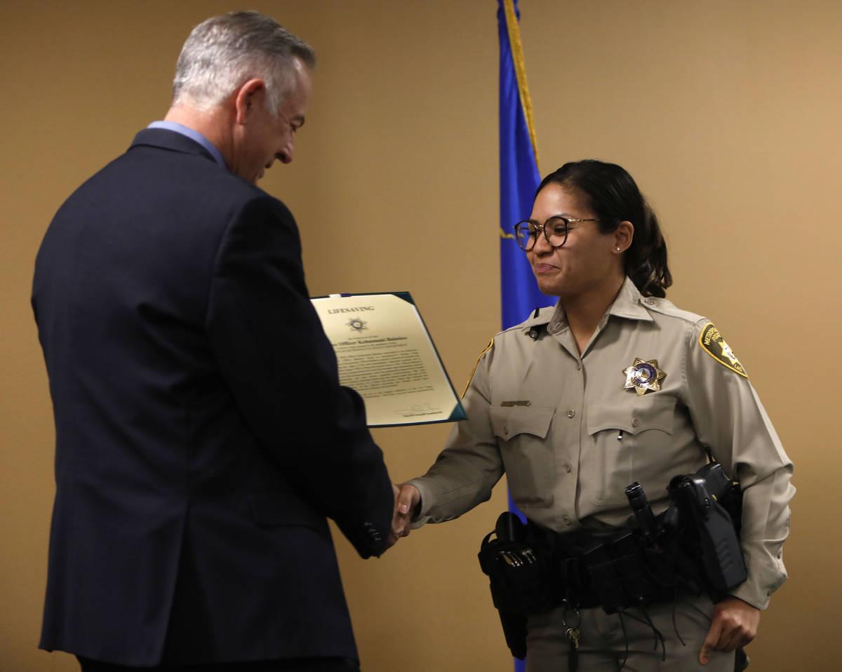 El alguacil del Condado Clark, Joe Lombardo, a la izquierda, estrecha la mano de la oficial Keh ...
