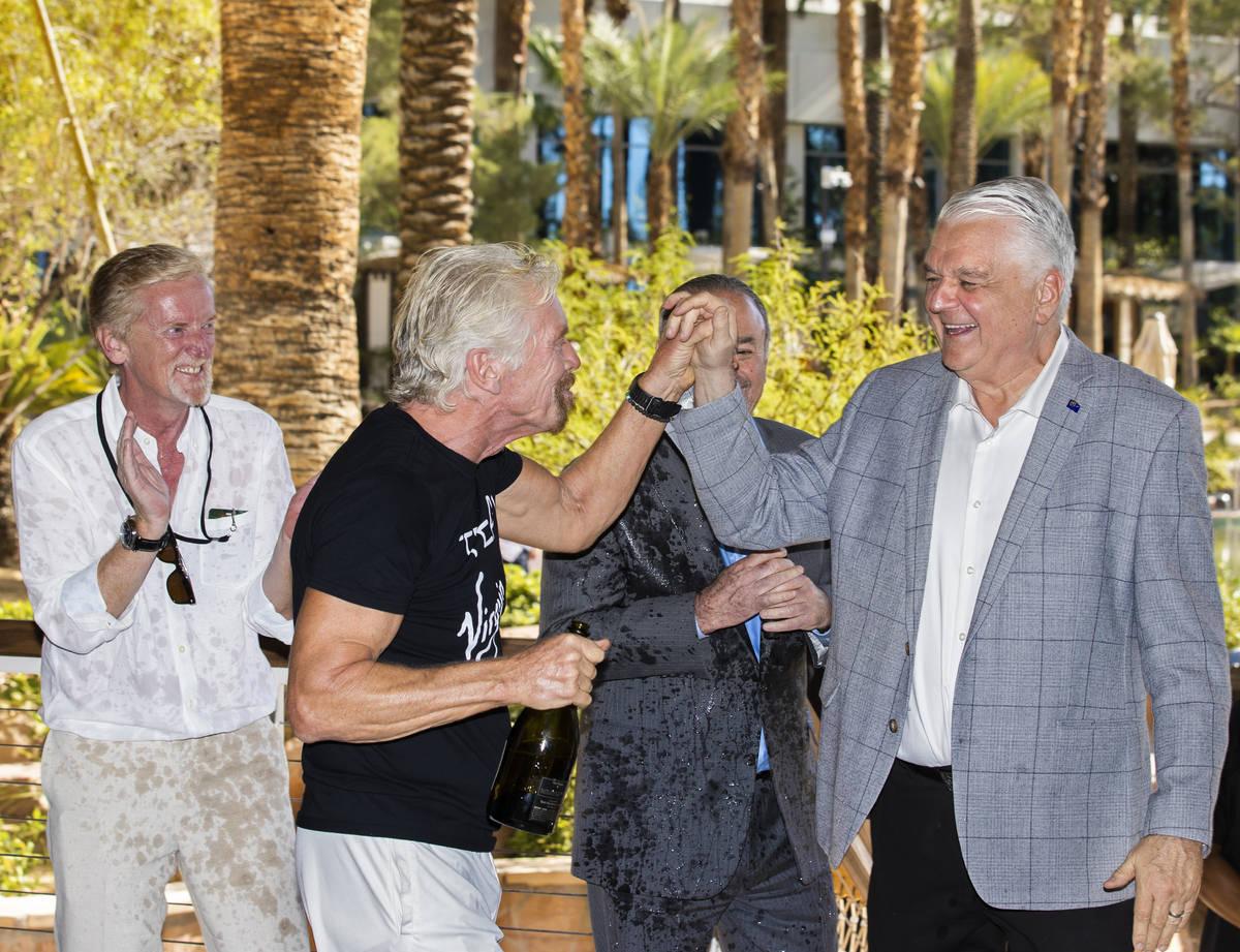 Sir Richard Branson, segundo por la izquierda, fundador de Virgin Group, choca los cinco con el ...