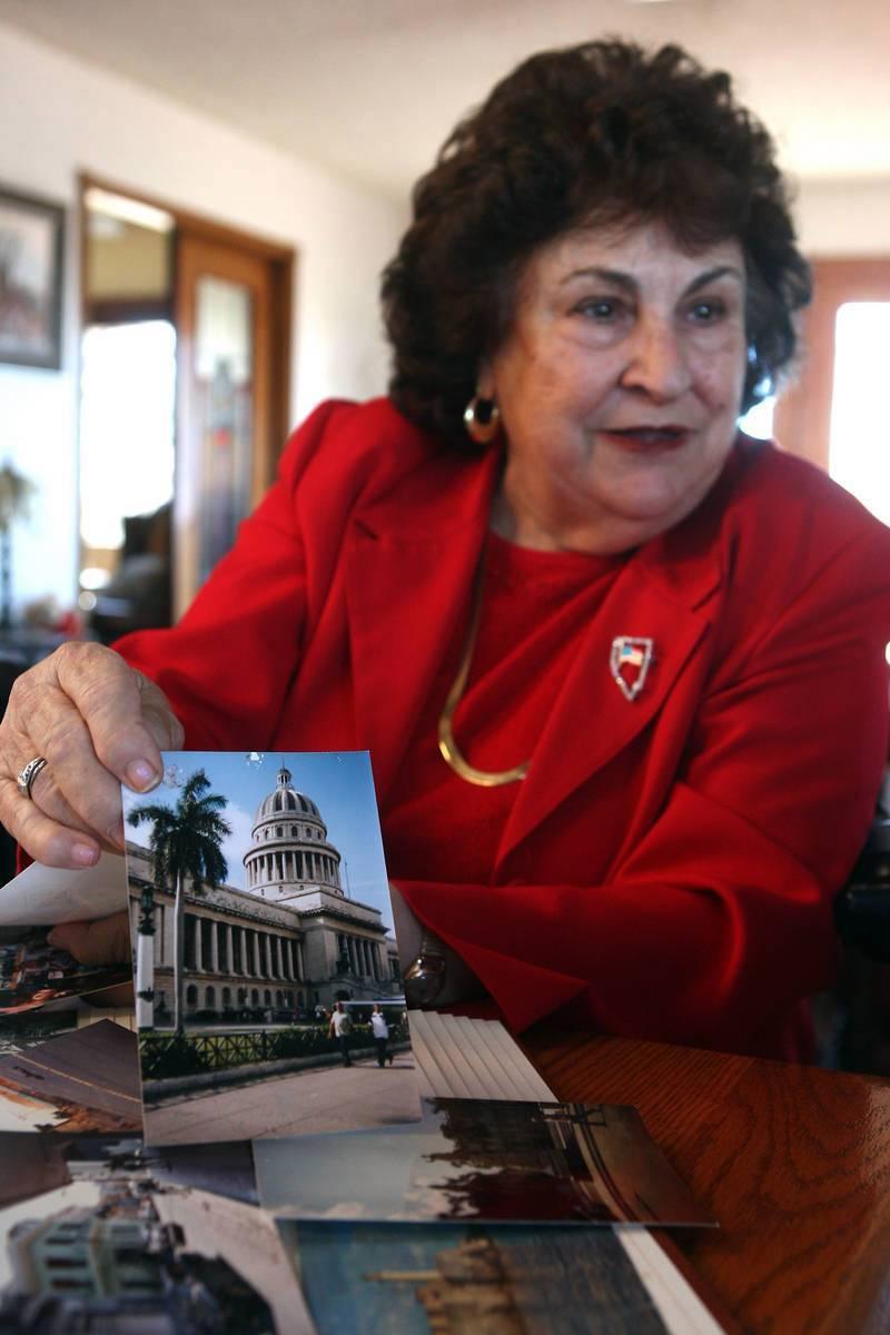 Liliam Lujan Hickey sostiene una fotografía del Edificio Capital en La Habana, Cuba, mientras ...