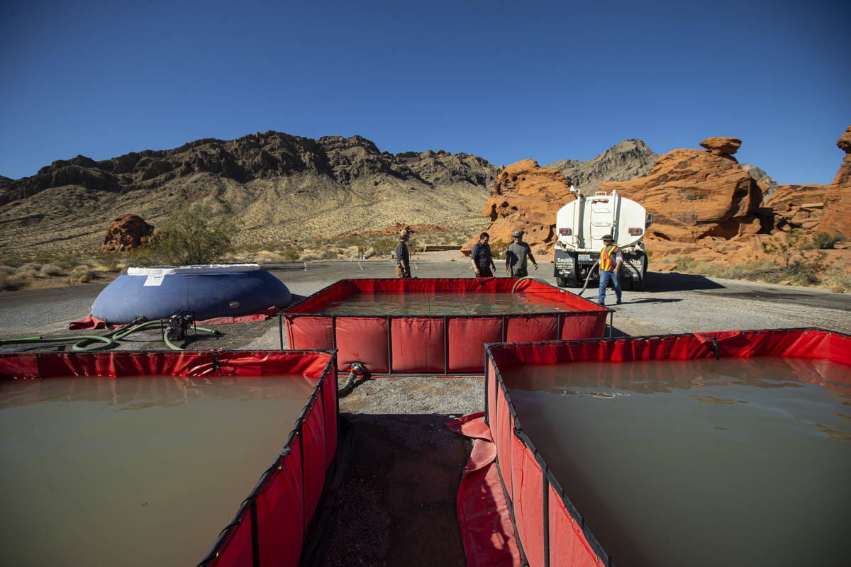 Water is prepared for transport by helicopter during an emergency water haul operation to reple ...